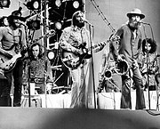 The Beach Boys performing on stage with an array of backup musicians. From the group, Al Jardine, Carl Wilson, and Mike Love are pictured.