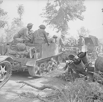 38th (Irish) Brigade - Universal Carriers of the 1st Battalion, Royal Irish Fusiliers pass a wrecked German Nebelwerfer rocket launcher near Ceprano, Italy, 28 May 1944.