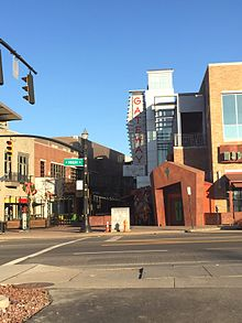 "A view across a signalized intersection, with a green sign opposite reading ""High Street"", to some buildings with an irregular, stylized entrance on one side of a pedestrian mall, lit by low raking sunlight. In the rear is a sign with ""Gateway"" on it in vertical red letters."