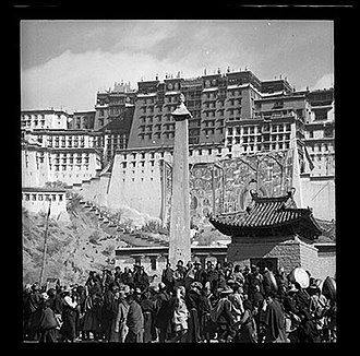 Potala Palace - The Sertreng ceremony photographed by Hugh Edward Richardson on April 28, 1949 with the double giant thangka banner on the white front of the palace.