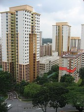 High-rise buildings stand next to each other besides a road. An apartment unit of the block on the right is highlighted in red.