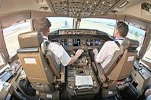 Кабина экипажа из-за кресел двух пилотов.  Центральная консоль находится между сиденьями, спереди - приборная панель с несколькими дисплеями, а свет проникает через передние окна.