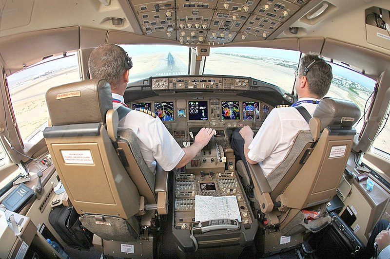 A flight deck, from behind the two pilots' seats. A center console lies in between the seats, in front is an instrument panel with several displays, and light enters through the forward windows.