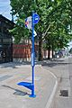 TriMet bus stop sign pole with single seat attachment, 6th & Glisan 2012.jpg
