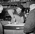 Twee mannen staan aan de bar terwijl de barkeeper een blikje opent, Bestanddeelnr 252-9499.jpg