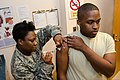U.S. Air Force Tech. Sgt. Pearl Gantt, left, with the 169th Medical Group, South Carolina Air National Guard, vaccinates Airman 1st Class James Gadson for an upcoming deployment at McEntire Joint National Guard 131208-Z-XH297-009.jpg