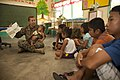 U.S. Marine Corps Maj. Grace Janosek, left, with the III Marine Expeditionary Force civil affairs element, reads to children while they wait to be seen by Philippine and U.S. military doctors during 130405-M-UY788-092.jpg