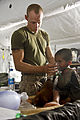 U.S. Navy Hospitalman Cameron B. Stieger with Headquarters and Service Company, 3rd Battalion, 4th Marines, Regimental Combat Team 8 holds an oxygen mask up for an Afghan child aboard Combat Outpost Ouellette 110530-M-DX675-014.jpg