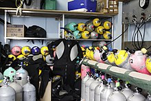 The interior of a dive shop filling station is shown, with a large number of cylinders standing on the floor or on wall racks. The filling panel is to the right and the cylinders being filled are resting on an angled rack below the panel.