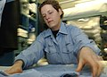 US Navy 021108-N-5576W-002 U.S. Navy Recruit Amy Pressley folds one of her utility shirts in preparation for packing her seabag, to depart recruit training.jpg
