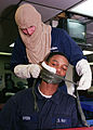US Navy 030501-N-9741A-002 Storekeeper 3rd Class Thomas R. Lawlor from Kerhonkson, N.Y. bandages a simulated facial wound on Fireman Shaun Green from Madison, Miss.jpg
