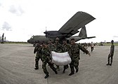 US Navy 050102-N-5362F-401 Soldiers from the Army of Jakarta carry a bag of rice and other disaster relief supplies from a C-130 Hercules at the Sultan Iskandar Muda Airport in Blang Bintang, Sumatra, Indonesia.jpg