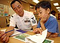 US Navy 050222-N-3019M-001 Culinary Specialist 1st Class Davidson Cervantes, assigned to the guided missile frigate USS Crommelin (FFG 37), helps a child read a book at Holomua Elementary School in Ewa Beach, Hawaii.jpg