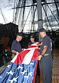 US Navy 050823-N-9076B-017 Chief petty officer selectees fold the Ensign aboard USS Constitution after a day of community relations' projects in the Boston area.jpg