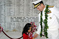 US Navy 051207-N-3019M-020 Chief of Naval Operations Adm. Mike Mullen hands his official coin to a Hawaiian girl aboard the USS Arizona Memorial.jpg