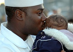 US Navy 060105-N-3019M-002 Boatswain's Mate 3rd Class Leroy Quinn kisses his son on the pier before departing aboard the guided missile destroyer USS Chung-Hoon (DDG 93).jpg