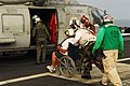 US Navy 060703-N-3729H-050 A civilian sports fisherman is wheeled to an SH-60F Seahawk assigned to the Eightballers of Helicopter Anti-Submarine Squadron Eight (HS-8) after being treated for head injuries.jpg