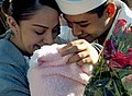 US Navy 071008-N-4163T-087 Gunner's Mate 3rd Class Mario Rodriguez greets his wife and newborn daughter during a homecoming celebration for guided-missile destroyer USS Milius (DDG 69).jpg