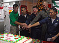 US Navy 071225-N-4774B-046 USS Tarawa (LHA 1), commanding officer, Capt. Donald R. Shunkwiler, center, and fellow Sailors cut a cake during a Christmas Day cake cutting ceremony.jpg
