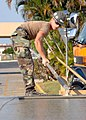 US Navy 081216-N-8816D-015 Builder 3rd Class Nicholas Whitaker uses a float to smooth wet concrete.jpg