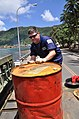 US Navy 091003-F-3798Y-136 U. S. Coast Guard Marine Science Technician 2nd Class Ryan Erpelding, assigned to U.S. Coast Guard Sector Hawaii, moves a barrel with hazardous waste towards the back of a truck in Pago Pago, American.jpg