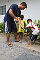 US Navy 100130-M-4593D-032 Lt. Gene Lattus, a priority material officer from Naval Station Pearl Harbor, plays with children during a visit to the Mercy Center orphanage.jpg