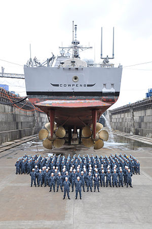USS Cowpens (CG-63) - The officers and crew of the guided-missile cruiser USS Cowpens (CG 63) pose for a group photo under the ship, July 2010.