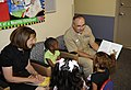 US Navy 100825-N-7032B-273 Rear Adm. C. Forrest Faison III, commander, Naval Medical Center San Diego, reads to children in the pediatrics clinic during a visit by U.S. Rep. Susan Davis to promote children's literacy.jpg