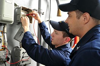 Interior communications electrician - Interior Communications Electrician Fireman Michael Colonna, left, from Sterling Heights, Mich., and Interior Communications Electrician 3rd Class Anthony King, from Nacogdoches, Texas, checks for voltage on an aircraft carrier elevator bell buzzer circuit during a dock trial aboard the aircraft carrier USS George Washington (CVN 73).