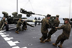 US Navy 120202-N-WV964-161 Marines assigned to the 31st Marine Expeditionary Unit (31st MEU) haul a 155 mm Howitzer onto the flight deck of the for.jpg