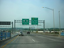 A multilane divided highway coming off a bridge with a parallel freeway. A set of two green signs is over the road, with the one on the left reading south U.S. Route 9 Route 35 Sayreville 1/4 mile and the one on the right reading Garden State Parkway south South Amboy Business center right lane 1/4 mile
