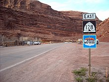 "Signpost assembly against a red sandstone backdrop. The signs on the post read, ""East, 128 (in a beehive shaped shield), and Scenic Byway""."
