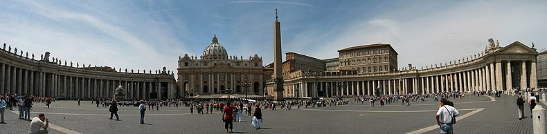Panorama showing the facade of St. Peter's at the centre with the arms of Berninis colonnade sweeping out on either side. It is midday and tourists are walking and taking photographs.