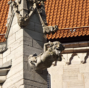 Gargoyle - Gargoyle representing a comical demon at the base of a pinnacle with two smaller gargoyles, Visby, Sweden