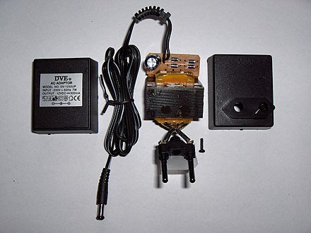 An AC adapter disassembled to reveal a simple, unregulated linear DC supply circuit: a transformer, four diodes in a bridge rectifier, and an electrolytic capacitor to smooth the waveform Wall wart opened.JPG