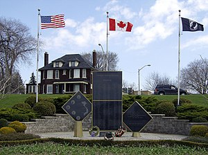 Large brown house behind Canadian and American flags