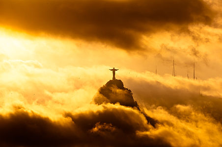 Christ the Redeemer statue on the Corcovado mountain during warm yellow sunset.