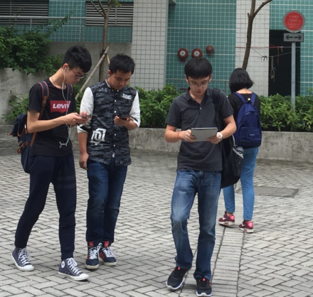 Social media websites are popular on mobile devices such as smartphones. Young people in Hong Kong using smartphones whilst walking.png