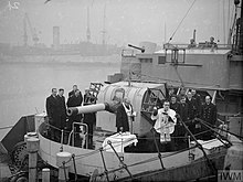 a black and white photograph of the main gun of ship with a group of men around it