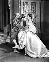 A barefoot man in Asian-style dress dances exuberantly with a woman in a formal gown with a large hoop skirt