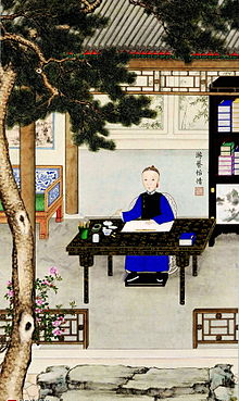 Color painting of young man wearing a deep-blue robe and a black sleeveless jacket sitting at a table holding a brush. A book, a brush with a cup, an inkstone, and a bowl filled with water are also placed on the table, which is itself black with golden or yellowish flower and leaf patterns. The table is disposed in a courtyard. There is a large tree in the left foreground that runs from bottom to top. On the right we see part of a bookshelf with books on it. Part of a wide chair appears on the left. In the background is the entrance to a small building.