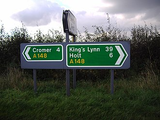 A148 road - Road Sign at the Junction of the A148 and Britons Lane to Beeston Regis. Holt is incorrectly displayed as a Primary Destination, though as Holt is the next major town, it is displayed for navigation purposes