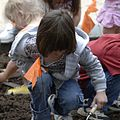 A young girl uses a trowel to dig a hole for plants in the pollinator garden.jpg