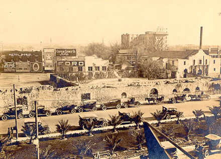 "The Alamo and Downtown San Antonio c. 1920. In the center of the surrounding area are the remains of the ""Long Barracks"" which had been covered by the Hugo and Schmeltzer building Alamo 1920.jpg"