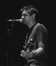 Steve Albini playing guitar, wearing a black t-shirt and ripped blue jeans