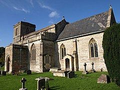 Stone building with square tower to left hand end. Foreground shows gravestones in grass area.