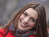 A photograph of Anne Hathaway; her head is tilted sidewards and she is wearing a red overcoat with a purple scarf.
