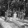 Arbeiders poseren met Hilde tijdens het bewerken van boomstammen, Bestanddeelnr 252-4811.jpg