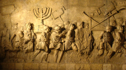Relief from the Arch of Titus in Rome depicting a menorah and other spoils from the Temple of Jerusalem carried in Roman triumph. Arch of Titus Menorah.png