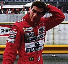 A man in red overalls, with his left hand at the rear of his head.